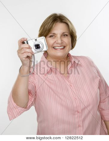 Caucasian middle aged woman taking photo with digital camera of viewer.