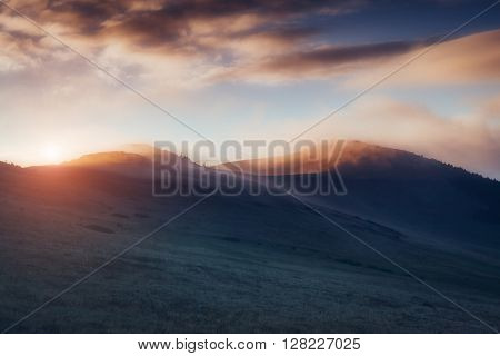 Magical hills glowing by sunlight at twilight. Dramatic scene and picturesque picture. Location place Carpathian, Ukraine, Europe. Beauty world. Retro and vintage style. Instagram toning effect.