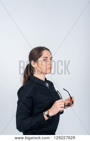 Beautiful young woman in a black shirt stands in profile and holds the glasses