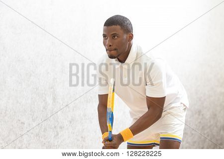Squash player playing against white background. Young black man with racquet playing squash and looking away.