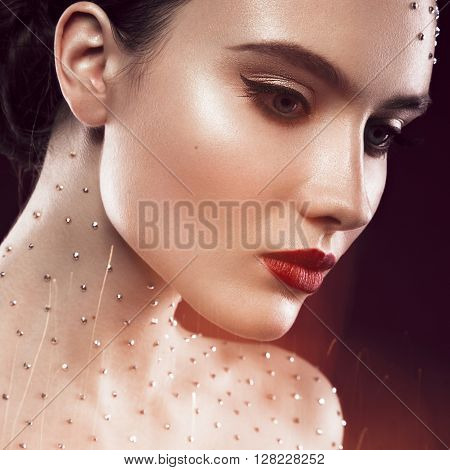 Portrait of a beautiful girl with a bright make-up, red lips and crystals on the body. The beauty of the face. Photos shot in the studio.