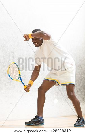 Squash player man touching his forehead after great game in squash. Handsome man holding racket and smiling.