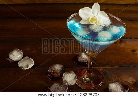 Cocktail Blue Martini on the dark wooden background. Blue cocktail. Blue Martini. Blue Hawaiian cocktail. Blue curacao liqueur. Blue margarita