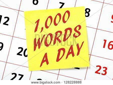 Reminder on a yellow sticky note posted on a calendar to write one thousand words a day for aspiring writers and authors