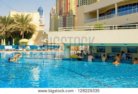 Dubai U.A.E. - November 12 2006: People in the pool bar of the Oasis resort in the new Marina quarter