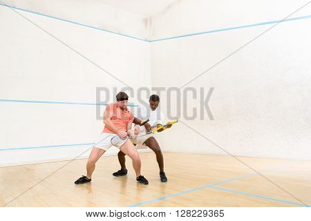 Men playing guitars on squash court. Handsome man playing game in squash and entertaining indoors after hard working day.