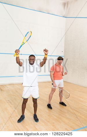 Handsome men playing squash on court all together. Best friends resting and relaxing with squash rackets indoors.