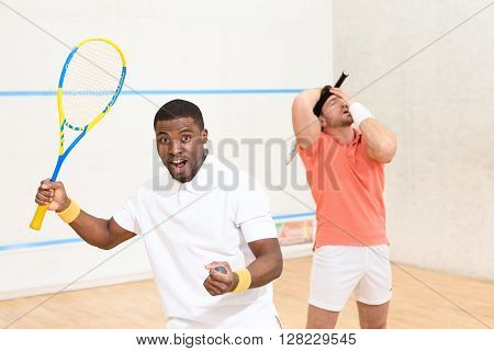 Young sportsmen playing squash on court and showing their positive emotions: astonishmen, excitedness, etc. Squash concept.