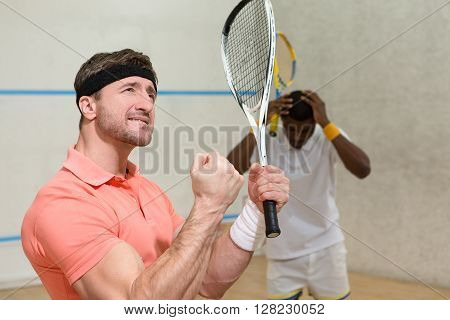 Cute men playing squash. Hansome muscular man in orange t-shirt expressing astonishment and excitedness after great battle in squash.
