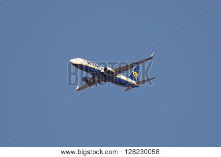 Torino Italy - April 18 2016: Ryan Air domestic flight n. FR8714 arriving at Torino International Airport from Bari Italy. Telephoto view from below of the flying Boeing 737-8 aircraft with clear blue sky.