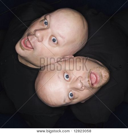 Aeriel view of Caucasian bald identical twin men sitting back to back making facial expressions.