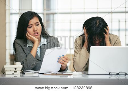 two businesswomen look hopelessly at their document with their hand on their head in office