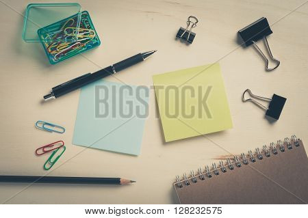 Sticky paper including blue and green color with blank area for text or message stick on wood table with pen pencil paper clips and notebook in morning time with vintage filter effect