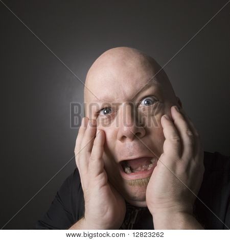 Caucasian mid adult bald man with hands to face making scared facial expression.