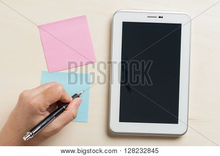 Young man writing with left hand on blue sticky paper beside small tablet pc with blank area on touchscreen on wood table