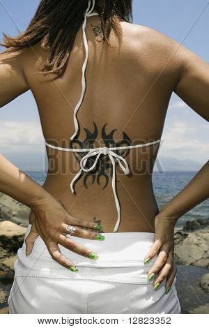 Rear view of multi ethnic young adult woman on beach with hands on hips and tattoo.