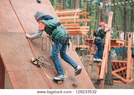 adventure climbing high wire park people on course in mountain helmet and safety equipment