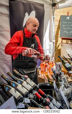 London United Kingdom - April 30 2016: Maltby Street Market in Bermondsey (located in railway arches SE1 Rope Walk). Great artisan street food stalls and bars. Wine vendor is pouring rose wine