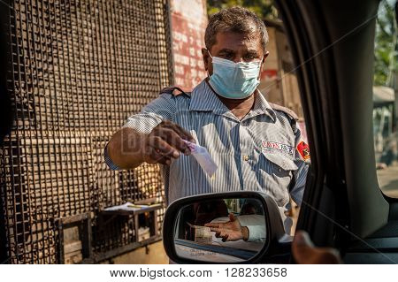 MADURAI INDIA - JANUARY 29 2014: A car parking attendant wearing a face mask issuing a ticket at a public car park in Madurai.