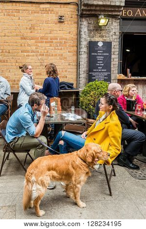 London United Kingdom - April 30 2016: Maltby Street Market in Bermondsey (located in railway arches SE1 Rope Walk). Great artisan street food stalls and bars. People with a dog are enjoying sunshine