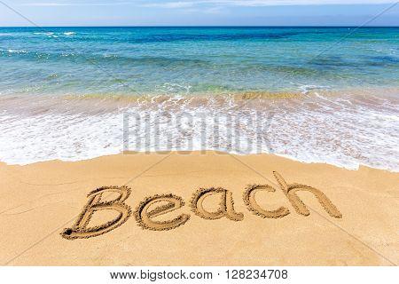 Word Beach written in sand of coast at sea