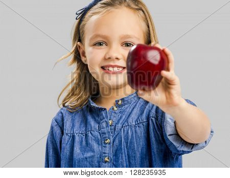Studio portrait of a beautiful cute girl holding a fresh red apple