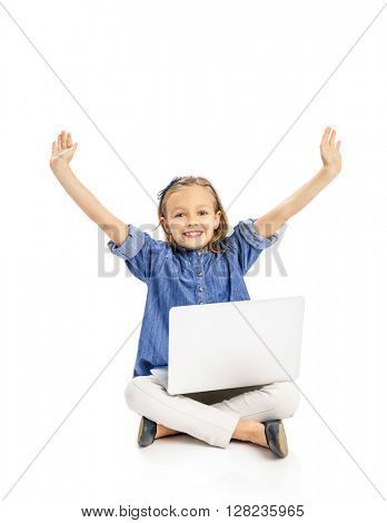 Happy little girl sitting on the floor and working a laptop