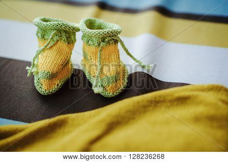 yellow and green handmade crocheted booties for a baby