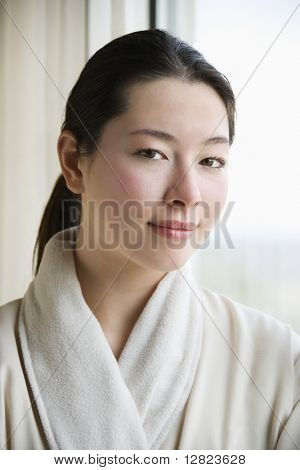 Taiwanese mid adult woman in bathrobe looking at viewer.