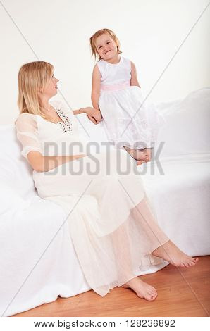 Young pregnant woman with little daughter