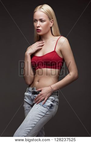 sexy fashion model with long hair, young European attractive, beautiful eyes, full lips, perfect skin is posing in studio for glamour vogue test photo shoot showing different poses. Picture taken in the studio on a gray background.