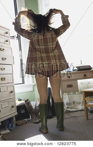Pretty young Asian woman in underwear and flannel shirt and rubber boots standing in bedroom.
