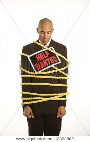 African American businessman wrapped in yellow rope wearing help wanted sign.