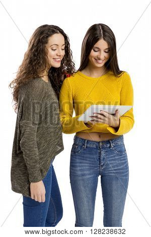 Studio portrait of two beautiful girls holding and showing something on a tablet