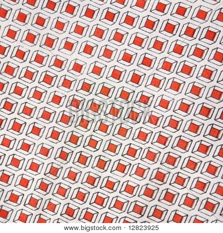 Close-up of vintage fabric with repetitive red cube designs printed on polyester.