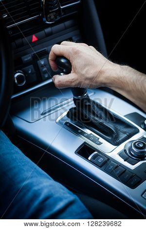 Detail of a hand pulling an automatic gear shifter in a new car.