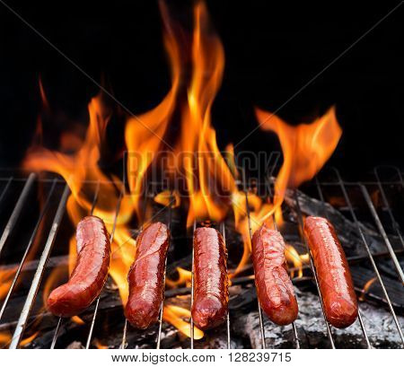 grill concept with flame. BBQ with fiery sausages on the grill