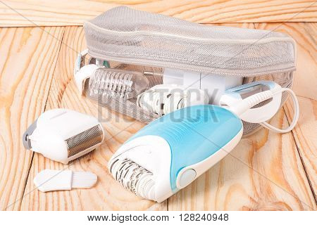 electric epilator hair on a light wooden background.