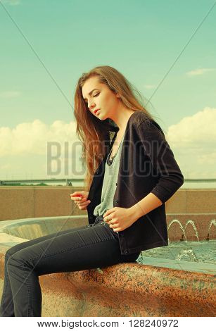 Lonely girl wants someone to talk. Wearing light gray sweater, black pants, an youg american woman sitting on red granite fountain, sad, depressed, listening to sad thoughts. Instagram effect.