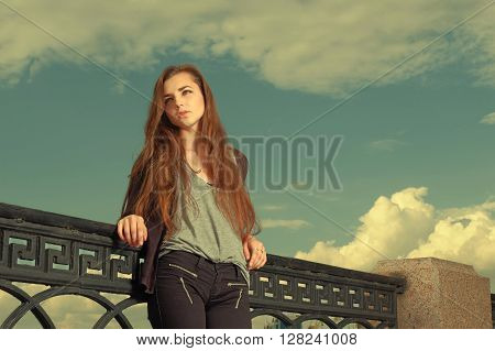 Lonely girl wants someone to talk. Wearing light gray sweater, black pants, an youg american woman standing by metal fence, frown, sad, depressed, lost in thought. Copyspace. Instagram effect