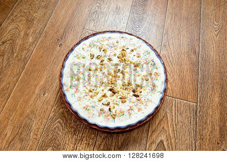 macro cake of house preparation with topping in a dish on a wooden background
