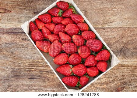 Fresh strawberries in a box on a wooden table
