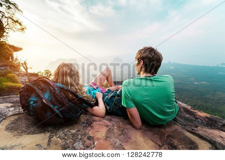 Young man and woman lying on the mountain at sunset