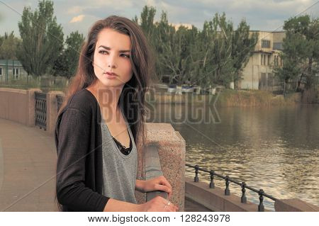 Pretty girl waiting for your. Wearing light gray shirt, black jacket, an young american woman standing by metal fence on pier in New York, frowned, sad, depressed, unhappy, looking back. Instagram effect.