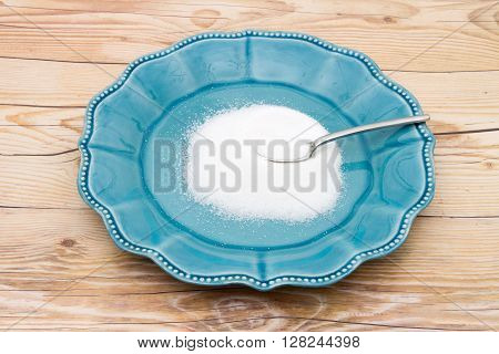 Teal Plate and spoon with a lot of sugar on a weathered wood background