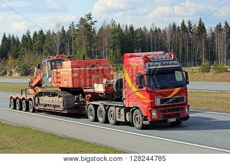 SALO, FINLAND - APRIL 29, 2016: Volvo FH truck transports Hitachi Zaxis 470 lch crawler excavator on lowboy trailer along freeway. The Zaxis 470 LCH is a large excavator of ca 48 tonnes of operating weight.