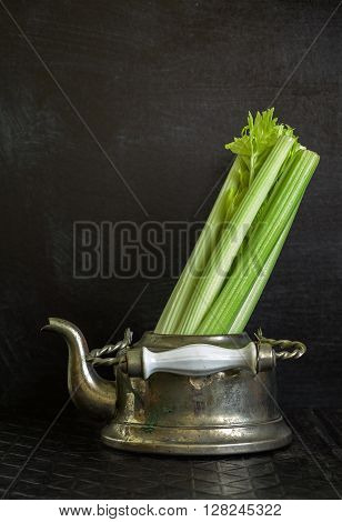 Vertical dark food background with old metal kettle and celery. Vintage food background. Lots of copy space.
