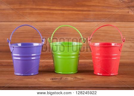 Beautiful buckets on the wooden background .