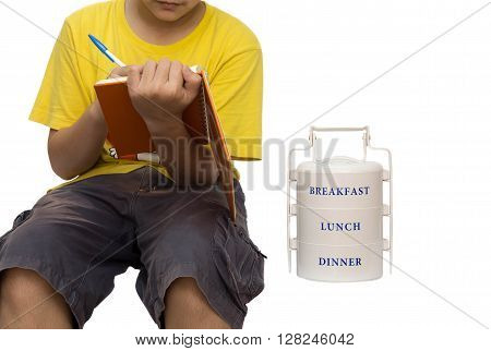 School boy writing a shot note and with food carrier on the side