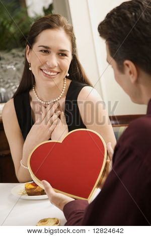 Mid adult Caucasian man giving a heart shaped box of chocolates to woman at restaurant.